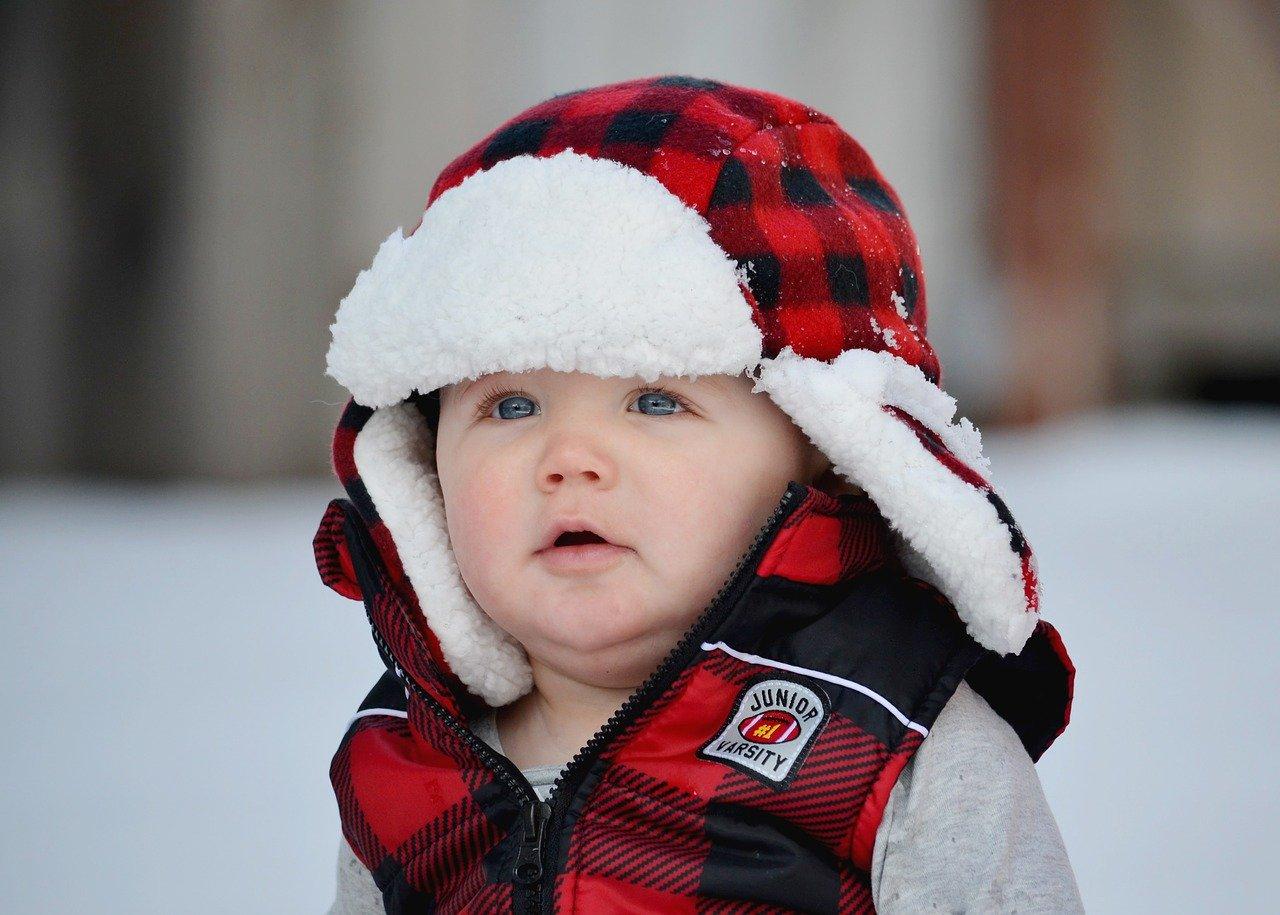 Achte beim Kauf eines Baby Schneeanzugs auch auf eine ausreichende Kopfbedeckung. Bei einiges Modellen ist diese bereits dabei.